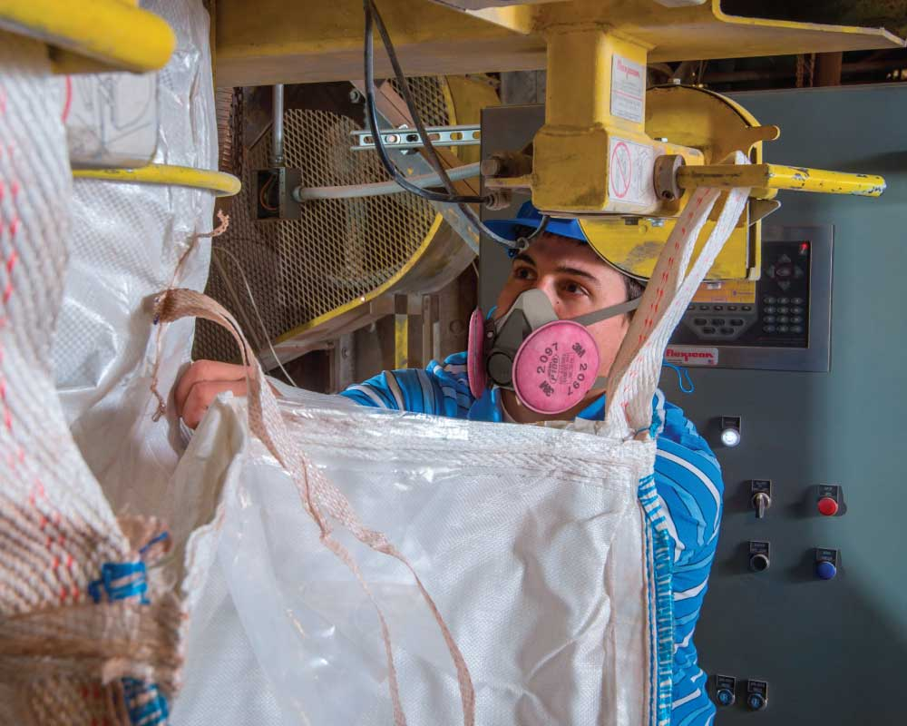 Person in respirator operating a hammer mill