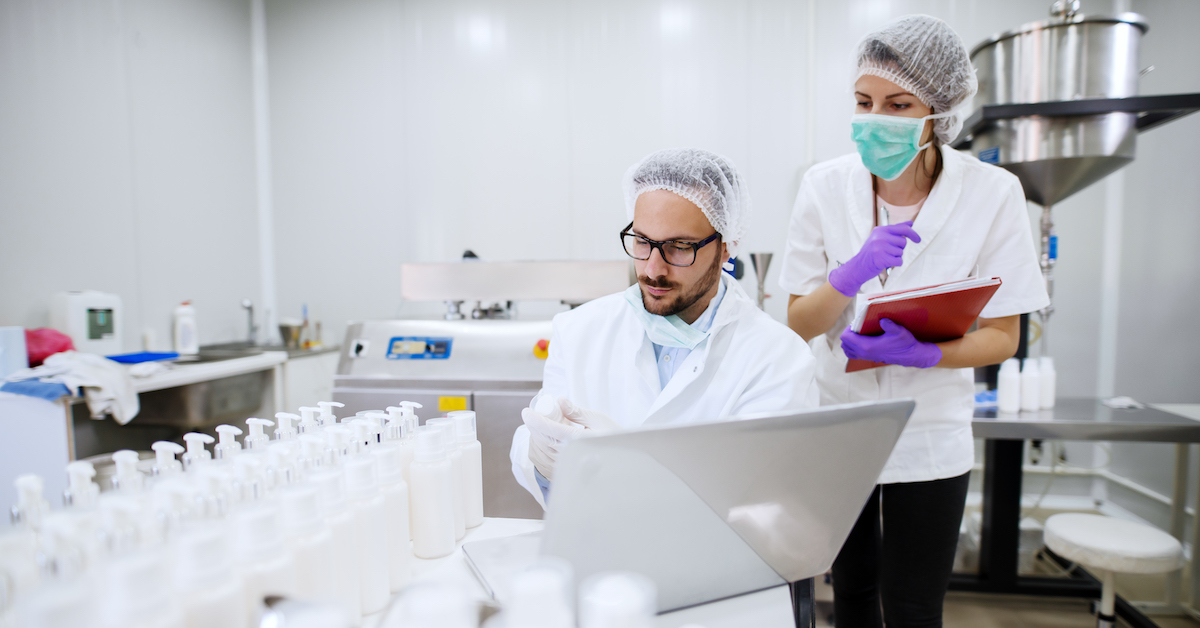 Two scientists working in a lab wearing protective clothing.